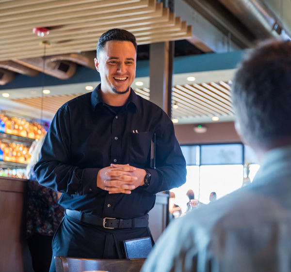 Happy and smiling server at customer's table