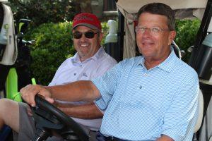 men posing by the golf cart