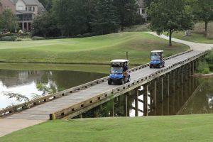 golf carts moving past bridge